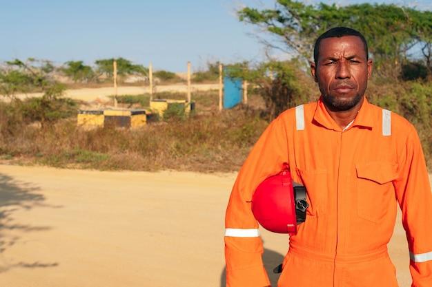 Koncepcja inżyniera lub technika. afrykański mechanik mężczyzna w pomarańczowym mundurze z hełmem na ramieniu.