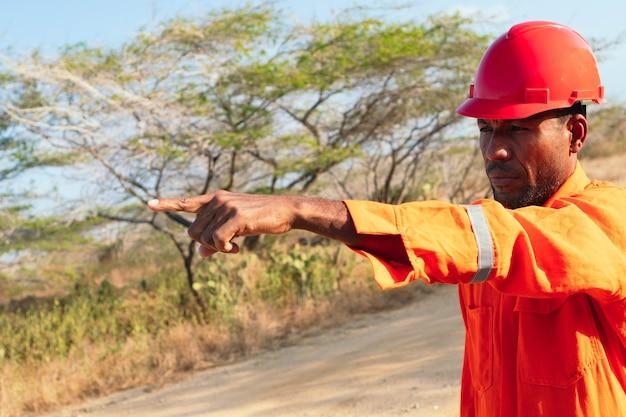 Koncepcja inżyniera lub technika. mechanik w pomarańczowym mundurze i palcem wskazującym.