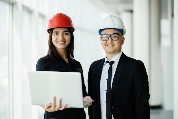 Koncepcja inżynierii i architektury. inżynierowie pracujący na budowie trzymając laptopa, architekt mężczyzna pracujący z inspekcją inżyniera kobieta w miejscu pracy dla planu architektonicznego
