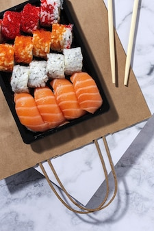 Koncepcja japońskiego jedzenia. różne sushi na wynos w pudełku. na wynos. dostawa. jedzenie morskie