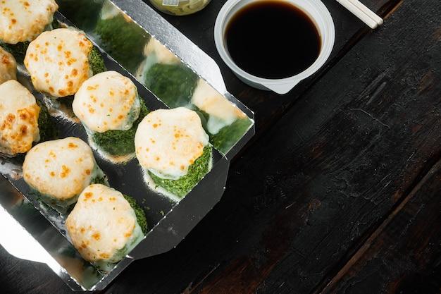 Koncepcja japońskiej żywności. catering, różne rodzaje sushi philadelphia rolls i pieczone bułeczki z krewetkami na starym ciemnym drewnianym stole