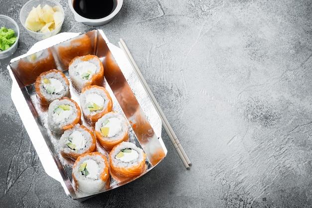 Koncepcja japońskiej żywności. catering, różnego rodzaju bułki sushi philadelphia oraz bułki z pieczonymi krewetkami, na szarym kamieniu