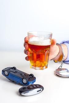 Koncepcja jazdy po pijanemu – piwo, klucze i kajdanki