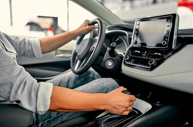 Koncepcja jazdy samochodem. kierowca przechodzi w tryb jazdy. ręka na transmisji stick zbliżenie