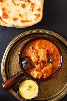 Koncepcja jedzenia domowe curry z kurczakiem tandoori masala z chlebem naan i sosem jogurtowym