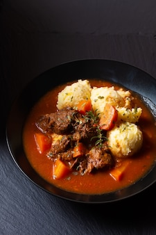 Koncepcja jedzenia spot fosuc domowy klasyczny gulasz wołowy z puree ziemniaczanym w czarnym naczyniu