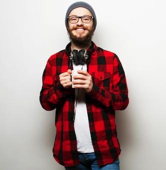 Koncepcja jedzenia, szczęścia i ludzi: młody brodaty mężczyzna z filiżanką kawy na szarej powierzchni