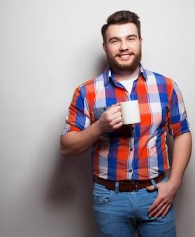 Koncepcja jedzenia, szczęścia i ludzi: młody brodaty mężczyzna z filiżanką kawy na szarym tle