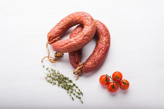 Koncepcja jedzenie, mięso i pyszne - kiełbaski z mięsa końskiego z pomidorami na stole