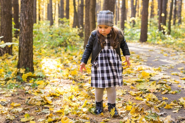 Koncepcja jesień, dzieciństwo i sezon - mała dziewczynka gra w parku jesienią