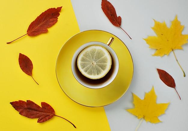 Koncepcja jesień, filiżanka ciepłej herbaty z cytryną, liście spadają.
