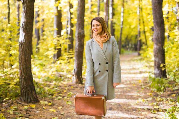 Koncepcja jesień, natura i ludzie - młoda piękna kobieta spaceru w parku z walizką