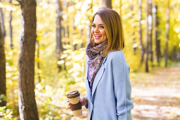 Koncepcja jesień, natura i ludzie - młoda piękna kobieta w niebieskim płaszczu, trzymając filiżankę kawy