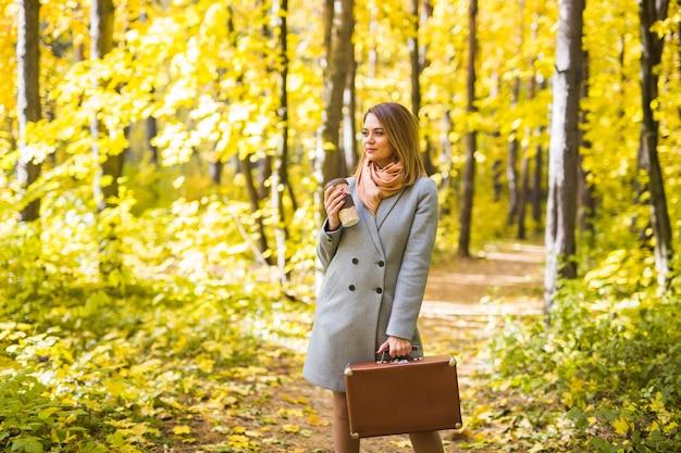 Koncepcja jesień, natura i ludzie - młoda piękna kobieta w szarym płaszczu, trzymając filiżankę kawy