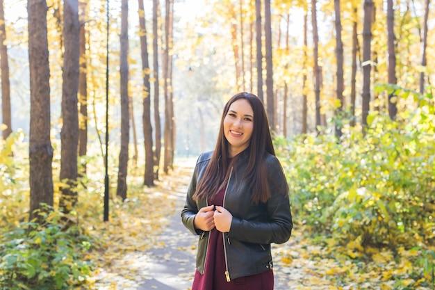 Koncepcja jesień, sezon i ludzie - młoda brunetka kobieta stojąca w parku na jesieni