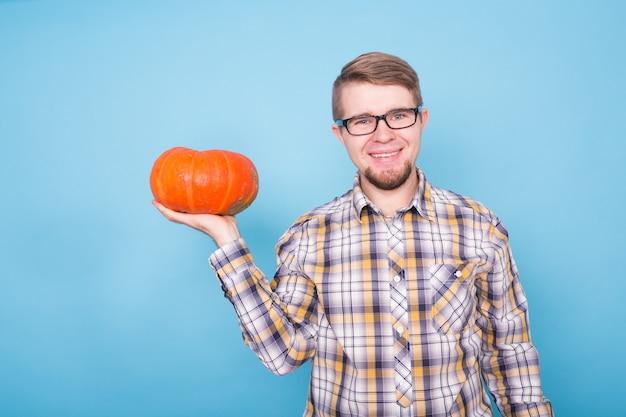 Koncepcja jesiennych ludzi na farmie młody człowiek rolnik z dynią w ręku uśmiechający się nad błękitem
