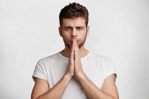 Koncepcja języka ciała i ludzi. przystojny, poważny młody mężczyzna trzyma dłonie razem, wierzy w szczęście przed ważnym wydarzeniem w życiu,
