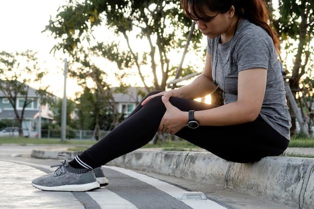Koncepcja joggingu, azjatycka kobieta masuje kolana w pozycji siedzącej ulicy.