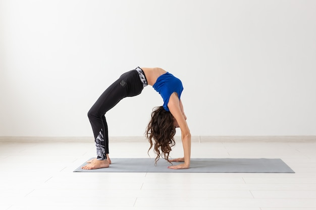 Koncepcja jogi, sportu, relaksu i ludzi - młoda kobieta praktykuje jogę w pomieszczeniu
