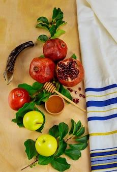 Koncepcja jom kippur. owoce z miodem i żydowskim talitem modlitewnym.