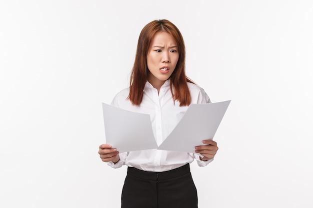 Koncepcja kariery, biznesu i kobiet. portret zaniepokojonej i niespokojnej pani biurowej panikującej podczas czytania dokumentów, otrzymywania okropnych wiadomości, pomieszanego projektu, skrzywienia się, biała ściana