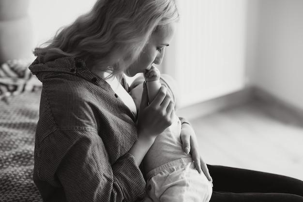 Koncepcja karmienia piersią. piękna młoda kobieta karmiących swoje małe dziecko na kanapie w domu, kopia przestrzeń