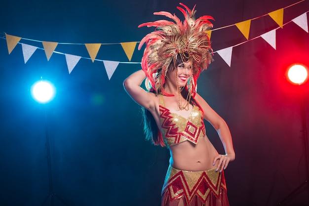 Koncepcja karnawału, tancerki i wakacji - piękna brunetka kobieta w kostiumie kabaretowym i nakryciu głowy z naturalnymi piórami i cyrkoniami.
