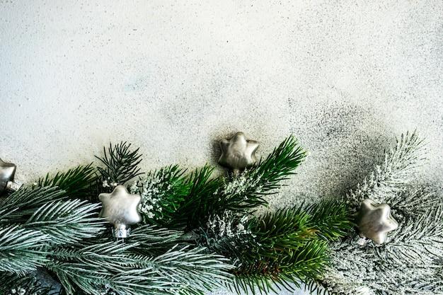 Koncepcja kartki świąteczne - rama wykonana z wiecznie zielonych gałęzi ze śniegiem i bombkami na kamiennym tle z miejsca na kopię