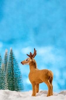 Koncepcja kartki świąteczne. świąteczna dekoracja jelenia zabawka z choinkami i śniegiem