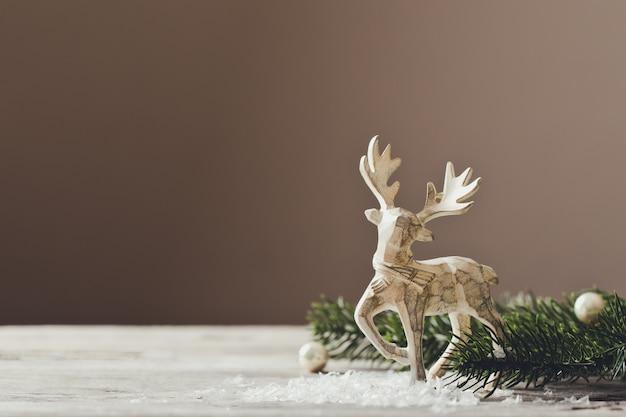 Koncepcja kartki świąteczne. świąteczna dekoracja jelenia zabawka z gałęzi choinki i śniegu.