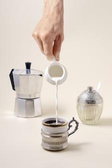 Koncepcja kawy - nalewanie mleka do filiżanki kawy, ekspres do kawy z gejzerem i shugar