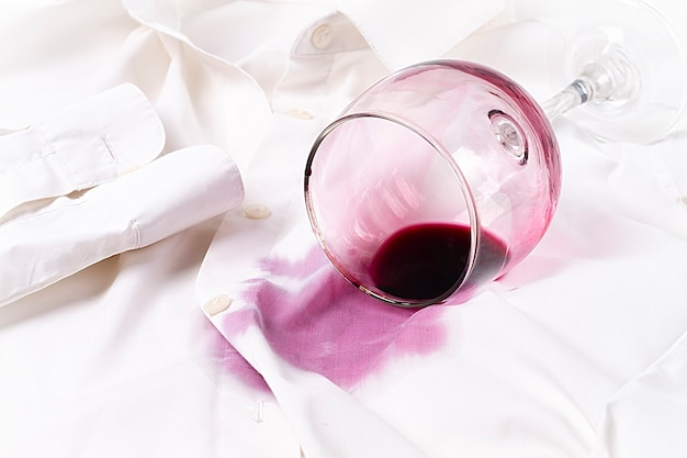 Koncepcja kieliszek do wina rozlany na białej koszuli bez ludzi w widoku poziomym z góry