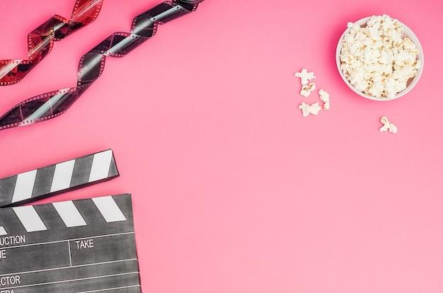 Koncepcja kina - klaps z popcornu i taśmy filmowej na różowym tle z miejsca na kopię.