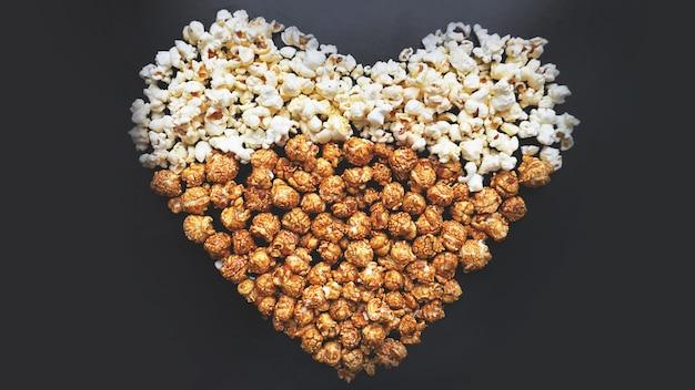 Koncepcja kina miłości popcornu ułożone w kształcie serca. różne popcorn ustawić tło. słodki i słony popcorn na czarnym tle.