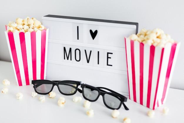 """Koncepcja kina - zbliżenie różowych pudełek w paski z popcornem, okularami 3d i podświetlanym pudełkiem z tekstem """"kocham film"""""""