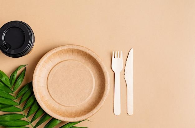 Koncepcja knollingu. ekologiczna jednorazowa zastawa stołowa zero waste, widok z góry, płaska leżała na brązowym tle.