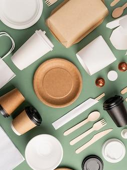 Koncepcja knollingu. ekologiczna jednorazowa zastawa stołowa zero waste, widok z góry, płaska leżała na zielonym tle. wzór