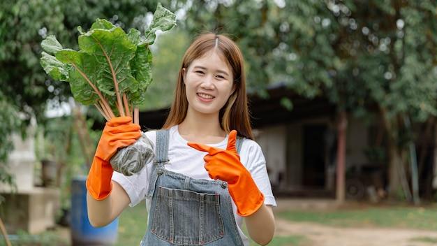 Koncepcja kobiece ogrodnik młoda kobieta szuka zabawy trzymając zielone warzywo, jego korzenie pokryte plastikową torbą z ziemią w środku.
