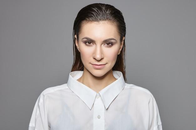 Koncepcja kobiecości, męskości i androgynii. pojedyncze ujęcie udanej pięknej młodej bizneswoman brunetka w stylowej formalnej białej koszuli patrząc z wyrazem pewności, uśmiechając się