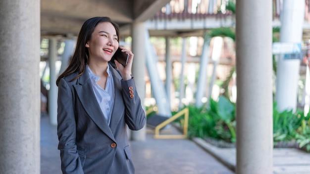 Koncepcja kobieta pracująca businesswoman dzwoniąc z klientem na temat działalności poza biurem.