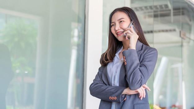 Koncepcja kobieta pracująca kobieta pracująca z uśmiechniętą twarz rozmawia przez telefon ze swoim partnerem biznesowym.