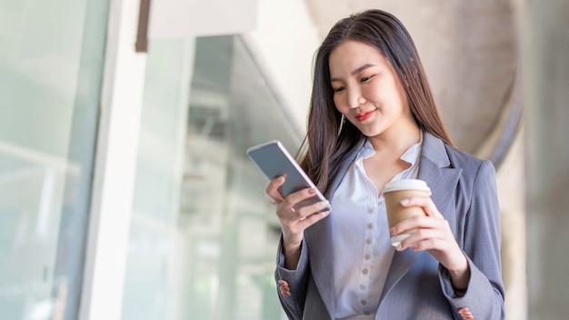 Koncepcja kobieta pracująca młoda kobieta menedżer uczestniczy w wideokonferencji i trzyma filiżankę kawy.