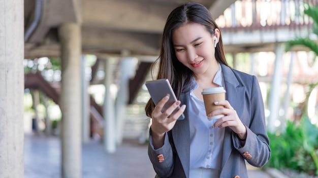Koncepcja kobieta pracująca młoda menedżerka trzymająca filiżankę kawy i komunikująca się z kolegą za pośrednictwem połączenia wideo.