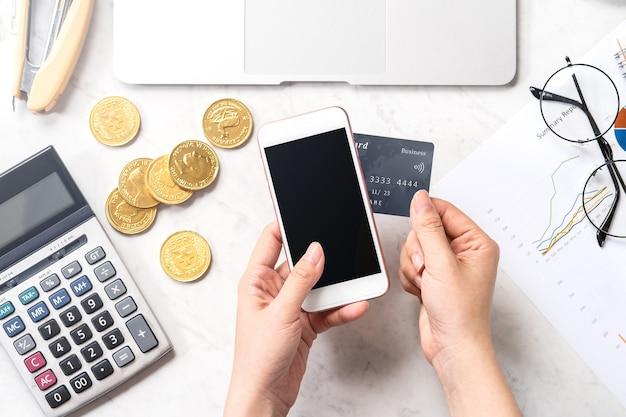 Koncepcja kobiety dokonującej płatności online kartą i smartfonem na białym tle na nowoczesnym marmurowym stole biurowym, makieta, widok z góry, miejsce na kopię, leżenie na płasko, z bliska