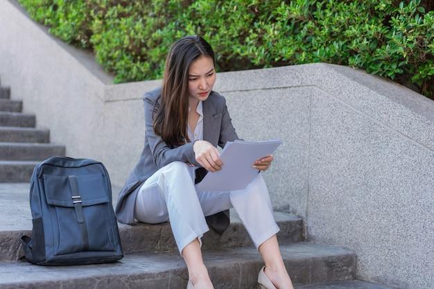 Koncepcja kobiety pracującej kobieta siedząca na stopniu patrząc na podania o pracę z uczuciem niepokoju i zdesperowania.