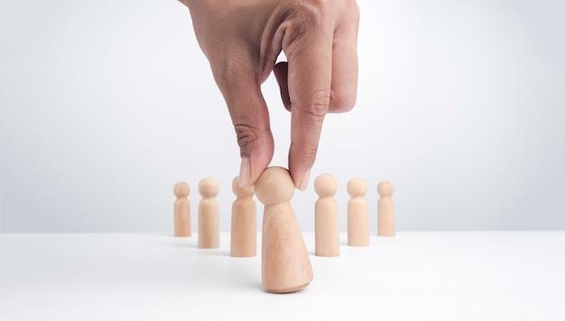 Koncepcja kobiety przywództwa. ludzka ręka trzymająca drewnianą figurę, kobietę i postawioną przed pracą zespołową prowadzącą do sukcesu, białe tło. wybrano liderkę.