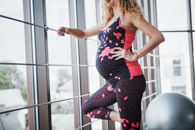 Koncepcja kobiety w ciąży uprawia fitness i prowadzi zdrowy tryb życia na siłowni