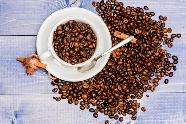 Koncepcja kofeiny. ładunek inspiracji i energii. kubek pełny brązowy palonej fasoli niebieskie tło drewniane. koncepcja kawiarni. menu napojów w kawiarni. przerwa na kawę i relaks. świeże palone ziarna kawy.