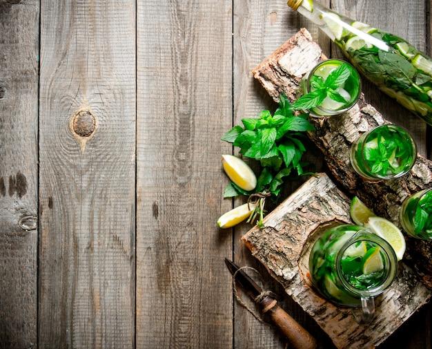 Koncepcja koktajlu mojito. koktajl na drewnianym stojaku z limonkami i miętą. wolne miejsce na tekst. widok z góry