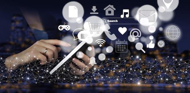 Koncepcja komunikacji i sieci. ręka dotykowy biały tablet z cyfrowym hologramem ikony mediów społecznościowych znak na ciemnym tle miasta niewyraźne. cyfrowa koncepcja online.